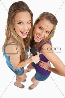 High-angle shot of two young beauty singing