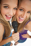 High-angle shot of two happy young beauty singing