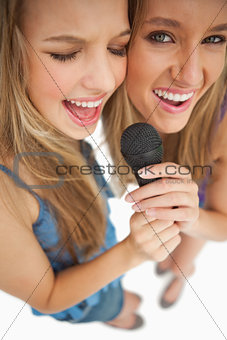 High-angle shot of two happy young blonde singing