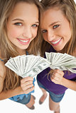 High-angle shot of two happy young beauty holding dollars