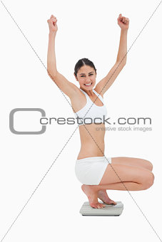Slim young woman sitting on a scales while raising her arms