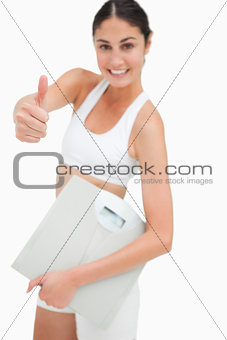 Slim young woman holding a scales the thumb-up