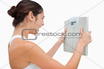 Young woman happy while holding a scales