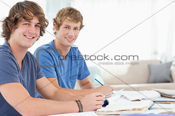 A pair of male students smiling as they both look at the camera
