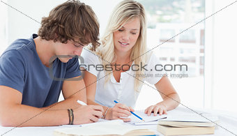 A man and woman working together at doing homework