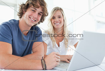 A smiling couple with a laptop looking at the camera