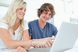 A smiling couple using a laptop while pointing at the screen