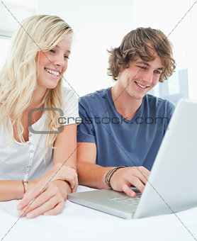 A smiling couple sit together as they surf the internet