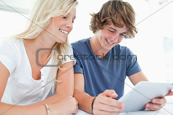 A smiling couple using a tablet together