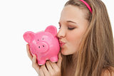 Close-up of a young woman kissing a piggy-bank