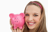 Close-up of a young woman holding a piggy-bank