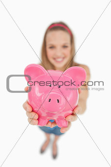 Fisheye view of a young woman tending a piggy-bank