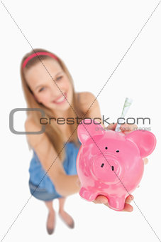 Fisheye view of a young woman putting money in a piggy-bank