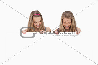 Close-up of two young women holding a blank board