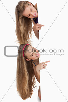 Two long hair students pointing behind a blank sign