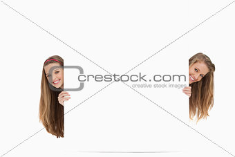 Two long hair women behind a blank sign