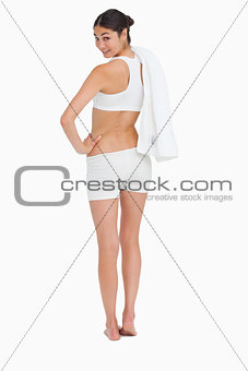Rear view of a smiling slim woman holding a towel