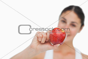 Close-up on a apple holding by a brunette