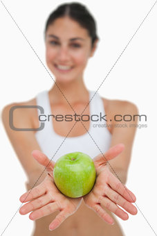 Close-up a green apple holding by a brunette