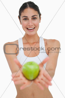 Close-up a brunette showing a green apple