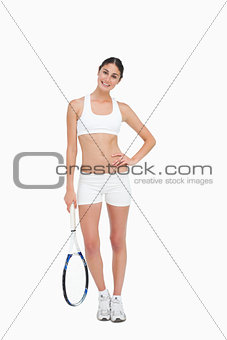 Slim brunette posing with a tennis racket