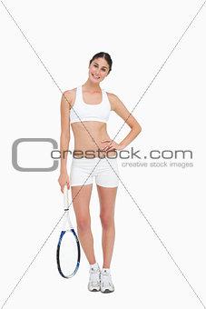Slim brunette posing with a tennis racket