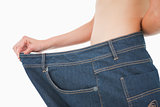 Close-up of a woman belly in a too big pants