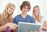 Three friends looking at the screen of the tablet