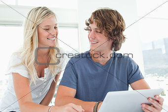 A smiling couple holding a tablet and looking at each other