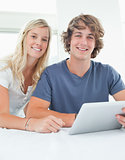 Close up smiling couple holding a tablet and looking at the came