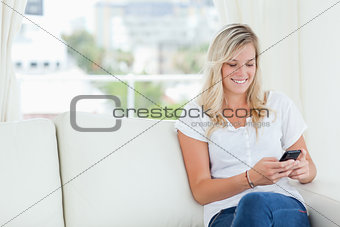 A woman sitting on the couch smiling as she uses her phone