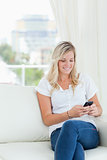 A woman smiles while using her phone on the couch