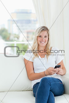 A smiling woman holding her phone as she sits and looks at the c