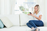 A woman sitting on the couch to the side as she uses her phone