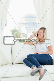 A woman sitting on the couch as she takes a call