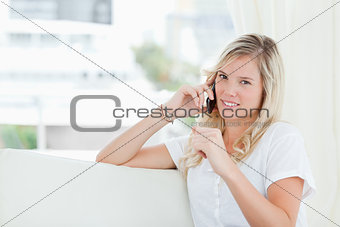 A woman looking at the camera as she talks on the phone