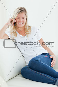 A woman sitting on the couch with her mobile as she talks and lo