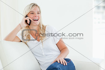 A laughing woman on her phone as she sits on the couch