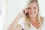Close up shot of a woman smiling as she talks on her phone 