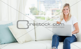 A woman sitting on the couch with a laptop in front of her as sh