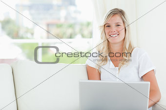 A smiling woman holding a laptop in her hands as she looks into