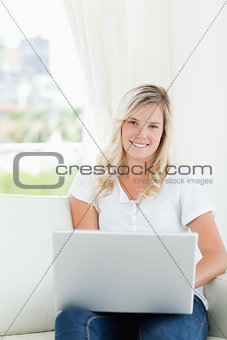 A smiling woman holding a laptop as she looks at the camera