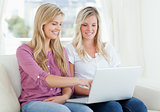 Two smiling women using a laptop as one points to the screen