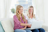 A pair of laughing women sitting on the couch with a laptop in h