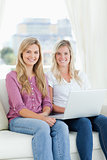 Two sisters sit together and smile with a laptop while looking a