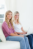 Two sisters sit on the couch with a laptop as they smile at the