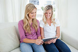 Two sisters sit on the couch as they look at a tablet