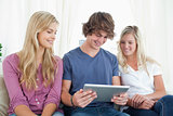 Three friends sit together as they look at a tablet pc 