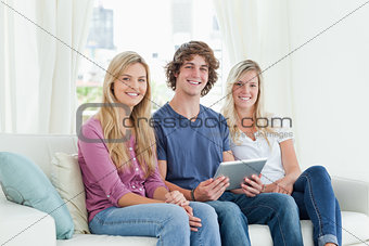 Three young adults look at the camera as they hold a tablet in t