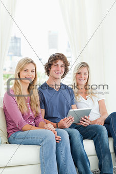 Two sisters and a brother sit on the couch looking at the camera